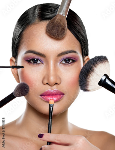 many hands applying make up on a woman - 85481338