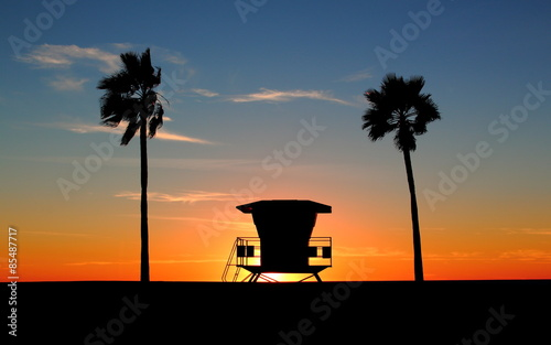 Silhouette of a California life guard station at sunset with Palm Trees