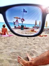 Spiaggia Vista Attraverso Occhiali Da Sole, Gambe In Primo Piano.
