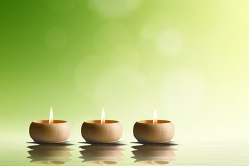 Spa concept. Three candles on green background.