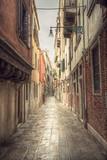 Fototapeta Uliczki - typical narrow alley in street of Venice (Venezia) at a rainy day, vintage style, Italy, Europe