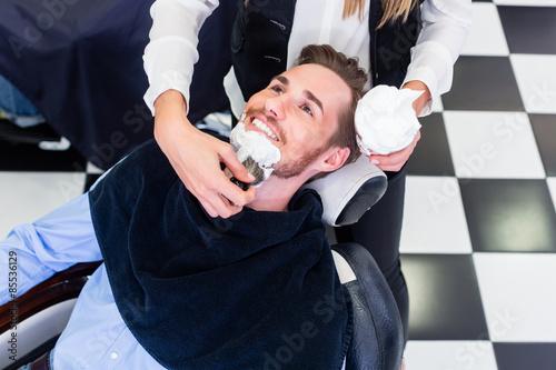 Fotografie, Obraz  Man getting beard shave in barber salon
