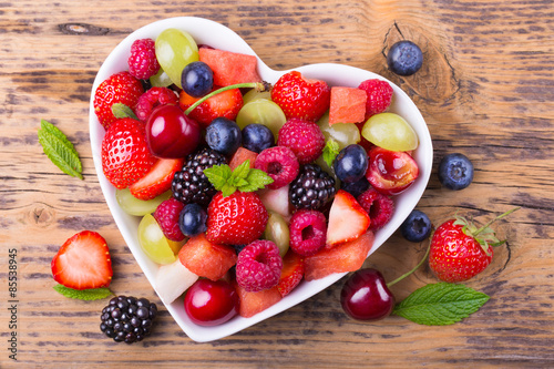 Obraz Fruit salad in heart shaped bowl - healthy eating - fototapety do salonu