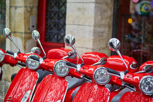 Red retro scooters parked on a Parisian street Fototapeta