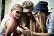 Girls having fun together outdoors using smart phone, lifestyle.