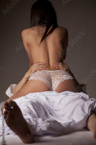 Fotografie, Obraz  a young couple in a sexual position on white sheets