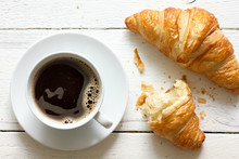 Croissants And Coffee In Cup On Rustic White Wood, From Above.