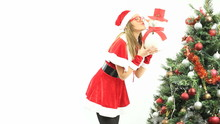 Santa Kissing Snowman - Hot Nerdy Mrs Santa Clause Kissing A Small Snowman Next To A Big Christmas Tree, Shot On White Background