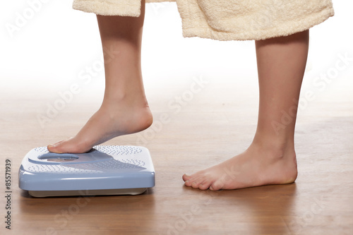 Fotografia  woman's legs on a domestic scale