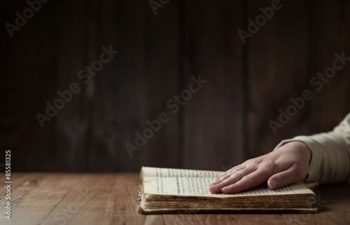 Fotografía  woman reading the bible in the darkness over wooden table