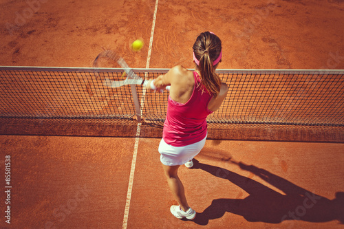 Young woman playing tennis.High angle view.Backhand volley. Poster