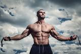 Muscular man under cloudy sky