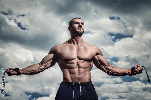 Fotografie, Obraz  Muscular man under cloudy sky