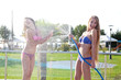 Two girls poured water from a hose