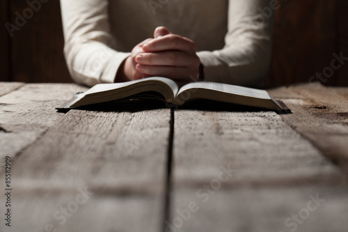Fototapeta Woman hands praying with a bible in a dark over wooden table