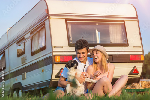 Young couple with a camper van Plakat
