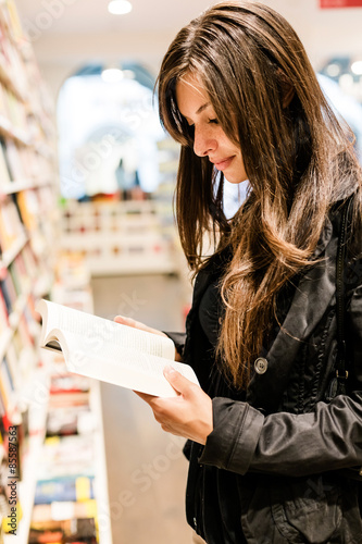 Photographie  Young woman reading books in a bookstore