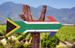 canvas print picture - South Africa Flag wooden sign with vineyard background