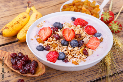 Healthy breakfast with fresh fruits, yogurt and granola on rustic wooden table Canvas Print