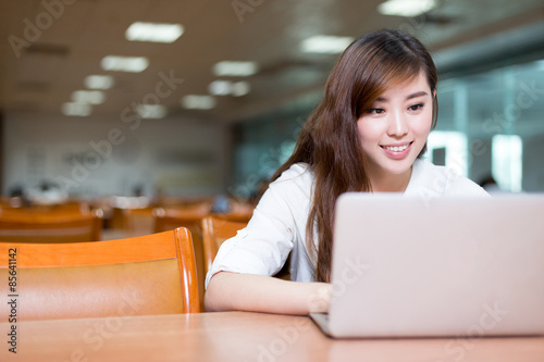Fotografia  Asian beautiful female student study in library with laptop