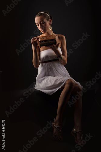 Photo  A girl acting Pandora as she opens the box