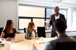 Black male executive leading meeting in conference room