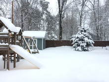 Snow Covered Backyard With Swingset