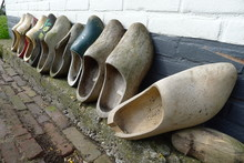 An Image Of Clogs In A Wall As Flowerpots Against Wall