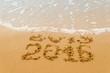 New Year 2016 - inscription 2015 and 2016 on a beach sand. Selective focus.
