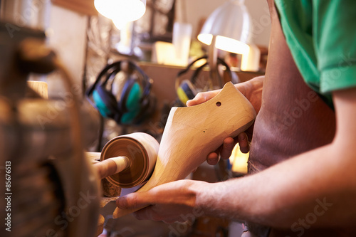 Hands of shoemaker shaping shoe lasts in a workshop