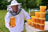 Fototapeta Zwierzęta - pszczelarz w pasiece prezentujący słoik świeżego miodu