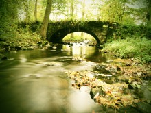 Old Stony Bridge Above Autumn River. Water Of Stream Full Of Colorful Leaves, Leaves On Gravel, Blue Blurred Water Is Running Over Boulders