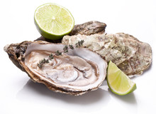 Raw Oyster And Lemon On A Whte Background.