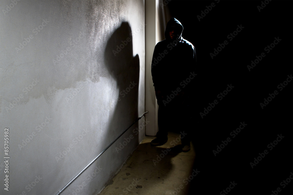 Fototapeta hooded criminal stalking in the shadows of a dark street alley