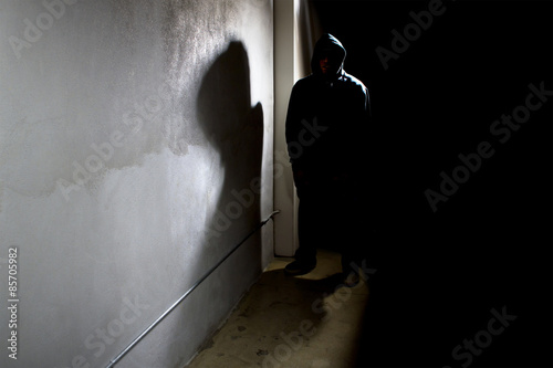 Fototapeta hooded criminal stalking in the shadows of a dark street alley obraz