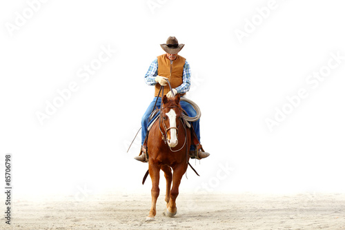 Obraz na plátne Mountain cowboy riding his horse in the dirt with a blank white background for text