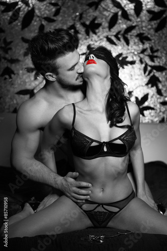 Obraz w ramie Sexy couple kissing on bed at night black and white