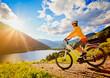 Leinwandbild Motiv woman with e-bike above a lake in sunset/e-power 11
