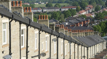 Red Chimney Tops Atop Row Of Stone Built Terraced Houses In Lancashire England