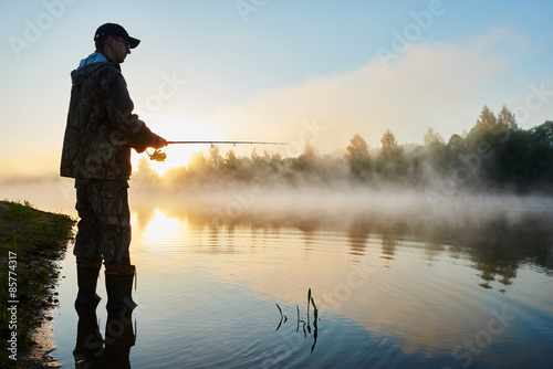 Fototapeta fisher fishing on foggy sunrise