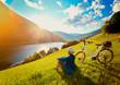 Leinwandbild Motiv woman resting above a lake with her e-bike/e-power 14