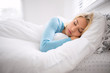 canvas print picture - Girl sleeping in late on weekend tired from long work week resting on plush white comforter