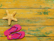 Slippers and starfish on wood