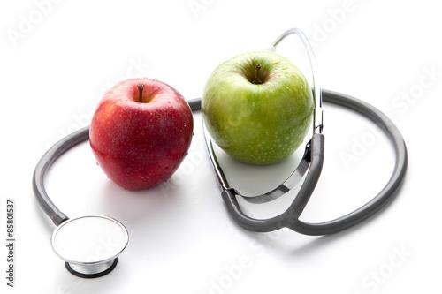Canvastavla Protege tu salud con una comida sana: estetoscopio y manzana en fondo blanco