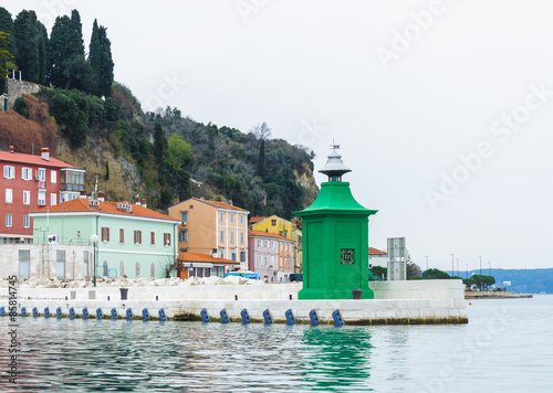 City on the water View of green lighthouse and buildings in city of Piran on back ground, Slovenia.