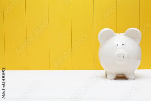Fototapeta Piggy bank against a yellow wall obraz