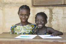Two African Ethnicity Children Smiling Studying In A School Environment
