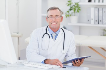 Smiling doctor looking at camera with clipboard