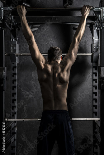 Fotografia  Bodybuilding, Young Athletic Strong Man showing Back Muscles working on Fitness