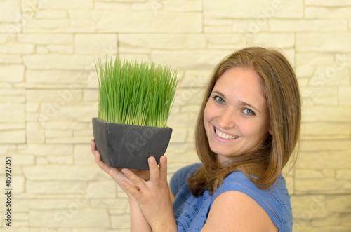 Valokuva  Junge Frau hält ein grüne Pflanze